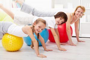 ילדים ואמם מתאמנים בבית על כדורי פילאטיס